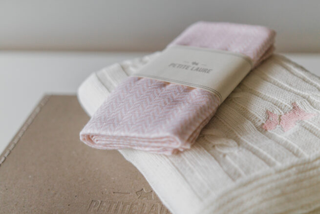 Baby gift set: Scandinavian baby blanket off-white with light pink dog and muslin baby bamboo swaddle, packed into our elegant suitcase with our logo.