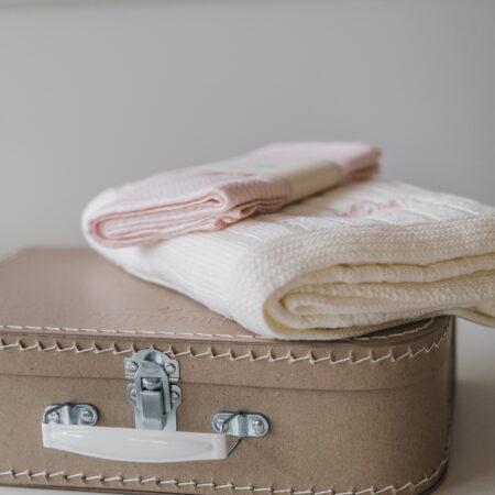 Zestaw prezentowy niemowlęcy zawiera: Kocyk niemowlęcy Scandinavian w kolorze śmietankowym z wyhaftowanym brązowym pieskiem oraz muślinową bambusową pieluszkę w brązową jodełkę.